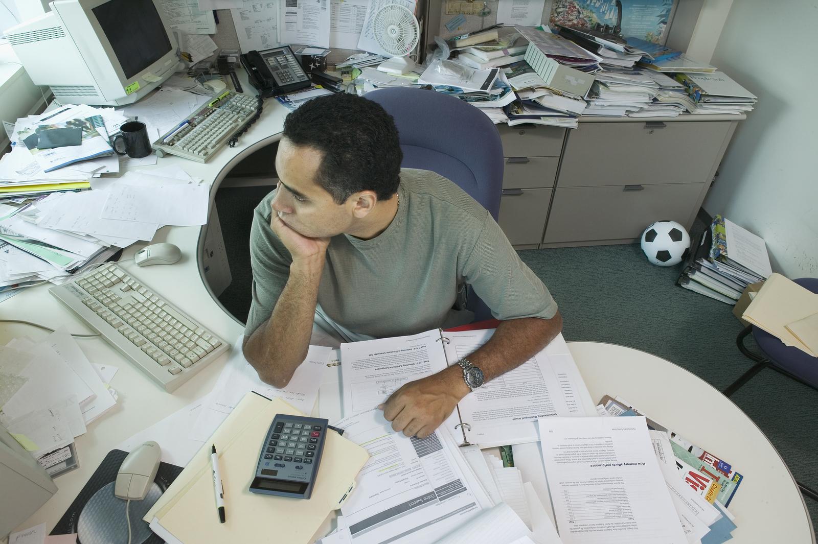 Businessman sitting at messy desk