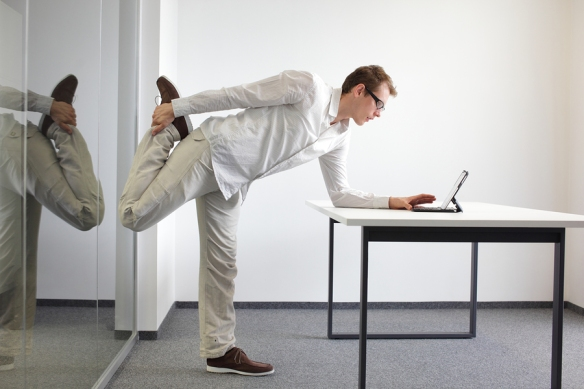 leg exercise at office work - standing man reading at tablet