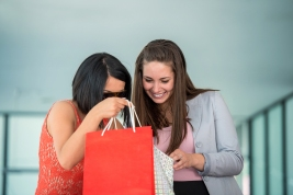 Excited successful women peeking in shopping bags smiling